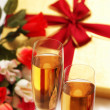 Stock Photo: Two wine glasses, gift box and flowers