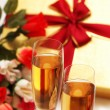 Two wine glasses, gift box and flowers — Stock Photo