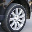 Car tyre of a shiny black car - Stock Photo