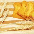 Stock Photo: Four toast pieces and wheat ears
