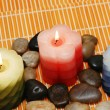 Three candles and pebbles — Stock Photo