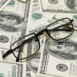 Reading glasses over  dollars — Stock Photo