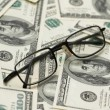 Reading glasses over  dollars - Stock Photo