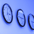 Stock Photo: Row of round clocks on wall