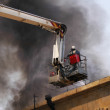 Firefighter on the firetruck boom — Stock Photo