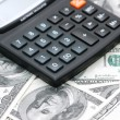 Accounting calculator over the dollars — Stock Photo