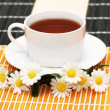 Cup of tea with herbs and daisies — Stock Photo