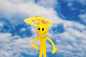 Smilie with yellow parasol — Stock Photo