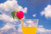 апельсиновый сок с соломой против неба — Стоковое фото