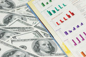 Business bar charts and dollar notes — Stock Photo