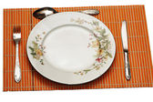 Plate and utensils served on the mat — Stock Photo