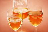 Three wine glasses on the biege — Stock Photo