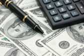 Calculator and pen over the dollars — Stock Photo