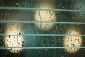 Water drops on the glass and blinds — Stock Photo