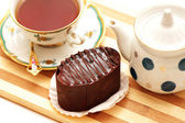 Chocolate cake, kettle and a cup of tea — Stock Photo