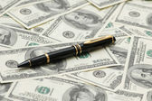 Black ballpoint pen over the dollars — Stock Photo