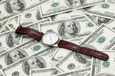 Hand watch over the hundred dollars — Stock Photo