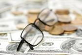 Reading glasses with coins — Stock Photo