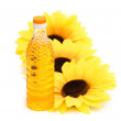 Three sunflowers and bottle of oil — Stock Photo