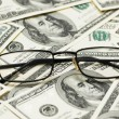 Reading glasses over dollars — Stock Photo #2684780