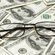 Reading glasses over the dollars — Stock Photo