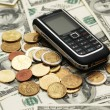 Mobile phone with coins and dollars — Photo