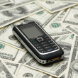 Mobile phone and dollar bank notes — Stock Photo
