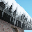 Row of icicles on a bright  day - Stock Photo