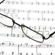Reading glasses over music sheets — Stock Photo #2686981