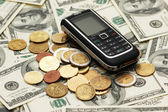 Mobile phone with coins and dollars — Stock Photo