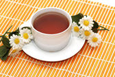 Cup of black tea and camomiles — Stock Photo