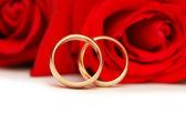 Två vigselringar och röda rosor — Stockfoto
