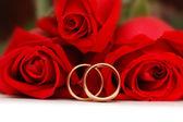Två guld vigselringar och rosor — Stockfoto