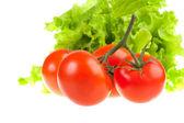 Tomates rojos y verdes hojas de ensalada. — Foto de Stock