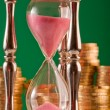 Hourglass and coins — Stockfoto #1568147