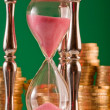 Hourglass and coins — Foto Stock