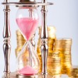 Hourglass and coins — Stock Photo #1568168