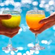 Glasses with juice against blue water - Stock Photo