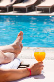 The woman at pool with a juice glass — Foto de Stock