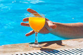 Hand and glass with orange juice — Foto de Stock