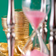 Hourglass and coins — Stockfoto