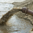 Stock Photo: Dirty water flows from pipe.
