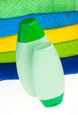 Bottles of shampoo and terry towels — Stock Photo