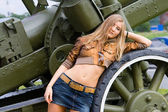 The young girl poses about a gun in a museum of arms, St.-Petersburg — Stock Photo