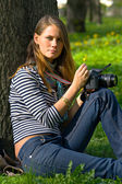 The girl-photographer in spring park — Stock Photo
