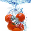 Tomato splashing in water - Stock Photo