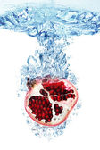 Pomegranate splashing in water — Stock Photo