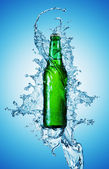 Beer bottle being poured in a water — Stok fotoğraf