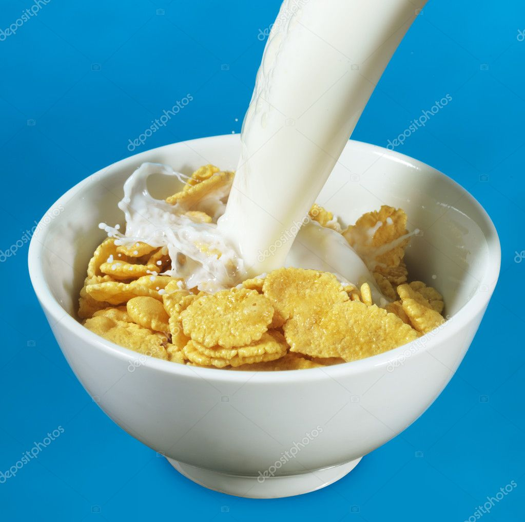 Bowl Of Cornflakes And Milk Milk pouring in...