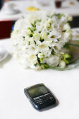 Wedding bouquet with the phone — Stock Photo